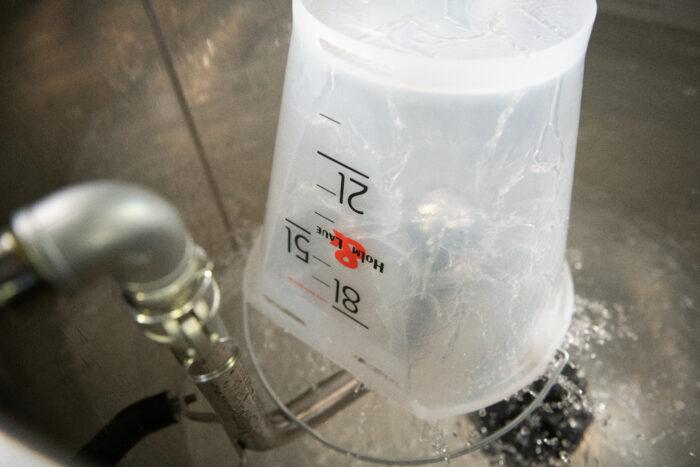 Auf diesem Foto ist der FlushMaster Sprühkopf zu sehen, der einen darüber gehaltenen Nuckeleimer reinigt.