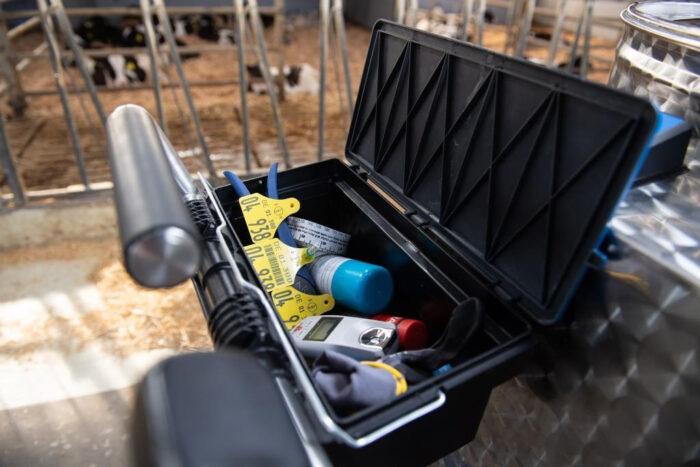 Dieses Detailfoto zeigt ein geöffnetes Handschuhfach am MilchTaxi. Darin lagern Hilfsmittel wie Ohrmarken, Brix Refraktometer und Kälbermaßband.