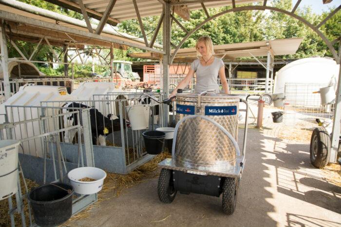 Dieses Bild zeigt eine Landwirtin mit MilchTaxi im KälberGarten. Sie dosiert Milch in einen Saugeimer.