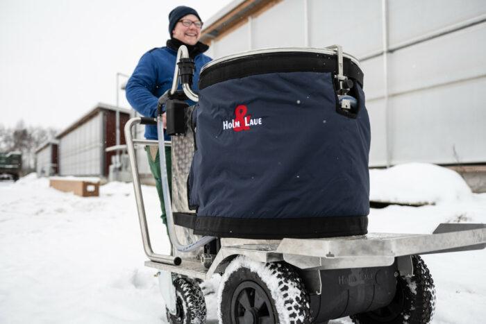 Auf diesem Foto ist ein MilchTaxi mit Mantel zu sehen. Es wird von einer Landwirtin durch den Schnee geschoben.